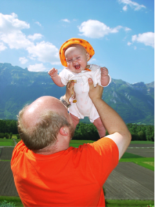 Man holding baby up in the air